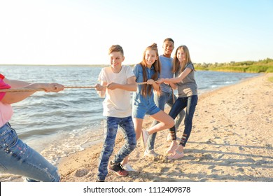 Group of children pulling rope during tug of war game on beach. Summer camp