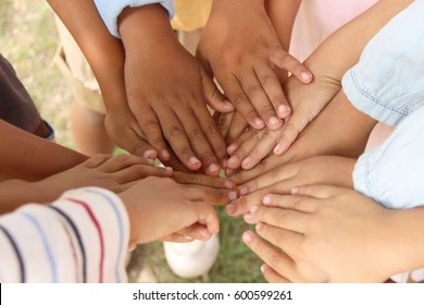 Group of children putting their hands together. diversity, race, ethnicity, international and people / Team work or Child experience concept. Selective focus.