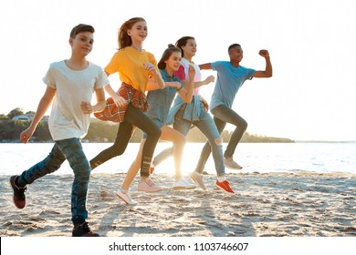 Group of children running on beach. Summer camp