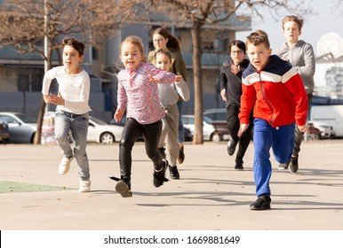 Group of children running on city street and having fun