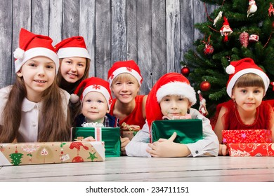 Group of children in santa claus hats with presents