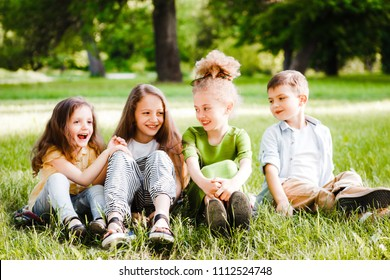 A group of children of school and preschool age are sitting on the green grass in the park.