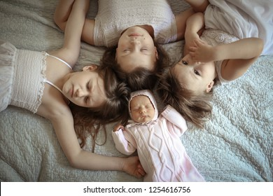 group of children sisters in the bedroom on the bed lie around, a top view. Lifestyle in the real interior. The large family.
