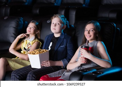 group of children sitting at the cinema, watching a film and eating popcorn. movie theater.