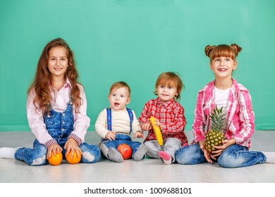 A group of children is sitting in a room. Useful Fruits. The concept of a healthy lifestyle, food, childhood, vitamins, vegetarianism.