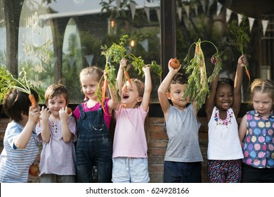 Group of children smiling and holding vegetable