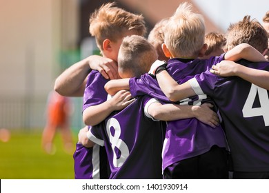 Group of children in soccer football team standing together before the final game. Boys motivating each other and building sports team spirit