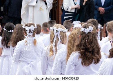 A group of children in solemn white clothes is waiting in front of the entrance to the church. Preparation for the first Holy Communion and for the Holy Mass.
