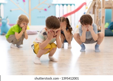 Group of children squatting on floor in daycare, having fun and playing hide and seek game, hiding the face with hands. Happy childhood concept.