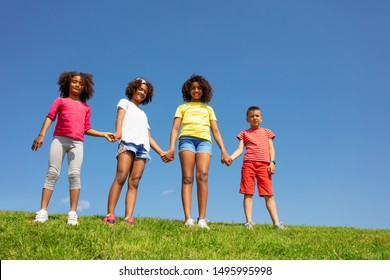 Group of children stand hold hand over clean sky