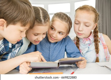 Group of children studying in the class together reading a book education childhood intelligence literature teamwork assignment homework kids elementary school friends friendship concept