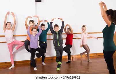 Group of children with teacher dancing ballet in dance hall