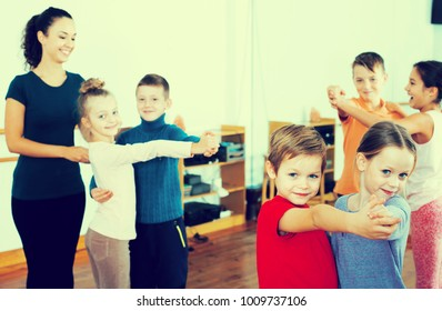 Group of children with teacher dancing pair dance in dance hall