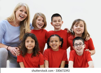 Group Of Children With Teacher Enjoying Drama Workshop Together