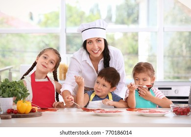 Group of children and teacher in kitchen during cooking classes