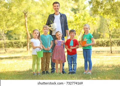 Group of children with teacher in park on sunny day