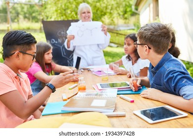 Group of children and teacher in tutoring chemistry class in summer school