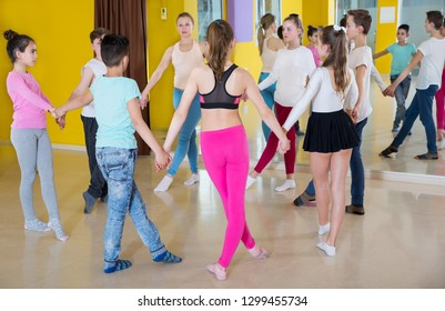 Group of children with their teacher holding hands and dancing in circle in dance school