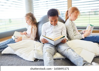 Group of children together read books in a primary school reading room
