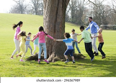 A group of children with two adults holding hands and dance around the trunk of a tree.