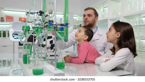 Group of Children Visit and Learn a Lesson about Science Laboratory, Researcher Teacher Talking about Chemistry Glassware Installation and Chemical Liquids Samples