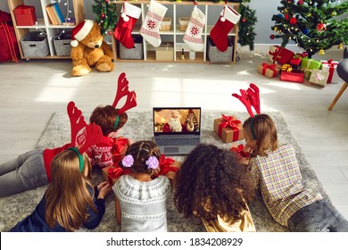 A group of children watching a video chat with Santa using a laptop in a decorated room during Christmas. Boys and girls 8-9 years talking with Santa Claus have a computer camera in a home.