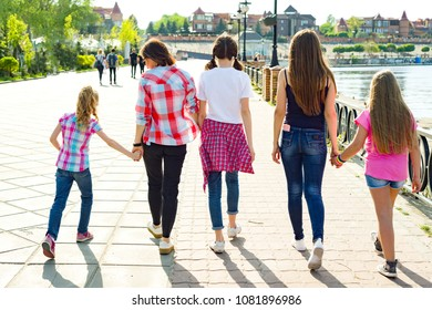 Group of children and women walking in the park.
