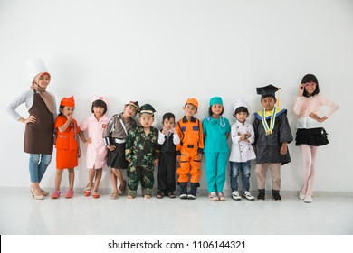 group of childrens dressed in costumes of different professions on white background together