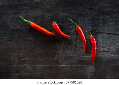 Group of chili peppers on top of a dark wooden table