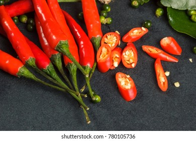 Group Of Chili Peppers And Sliced On Black Tablecloth. Vegetables,  Ingredient Background.