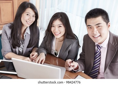 Group of Chinese business people smiling to camera in the office