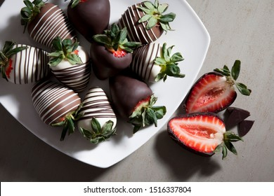 group of chocolate covered strawberries on white plate and light background, sliced chocolate covered strawberry, valentines day dessert, romantic, food gift