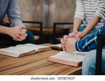 group of christianity  sitting around wooden table with open blurred bible page and praying to God together