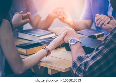 Group of Christians are congregants join hands to pray and seek the blessings of God, the Holy Bible. The cross symbol. They were reading the Bible and sharing the gospel with copy space.