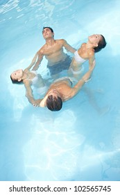Group in a circle doing water yoga in swimming pool