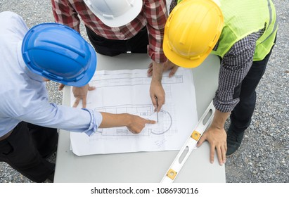 Group of civil engineer or architect, safety helmet and green reflective vest, working on construction site, blue print discussing, Real estate , construction industry and business concept.