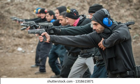 Group of civilian practice gun shoot on target on outdoor shooting range. Civilian team weapons training