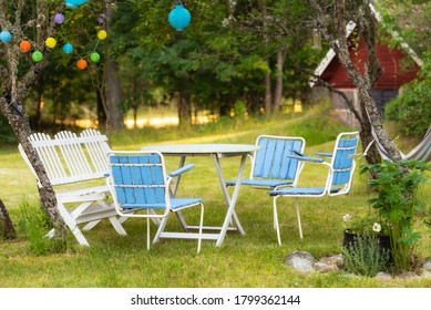 Group of classic Swedish garden furniture from the 1950s in a garden in Sweden. Colorful lanterns on the trees create a dreamy atmosphere in the dark.