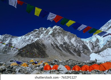 Group of climbers ' bright color tents on the Khumbu glacier in area of Everest base camp with colorful prayer flags and himalaya mountain range in background during a clear blue sky day