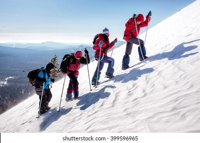 group of climbers climb the steep slopes of the snow-capped mountains on a clear day