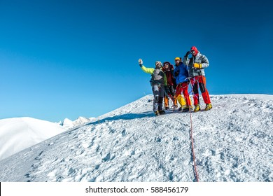 Group of Climbers in protective insulated Outwear alpine Gear and Ropes rising Hands enjoying the Victory against severe high Altitude Mountain
