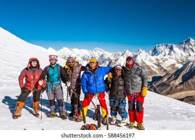 Group of Climbers in protective insulated Outwear alpine Gear and Ropes embracing celebrating the Victory against severe high Altitude Mountain