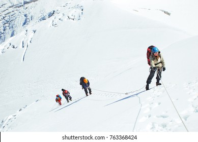 Group of climbers reaches the top of mountain peak. Climbing and mountaineering sport. Nepal mountains.