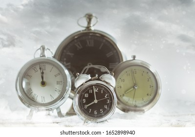 Group of clocks against a confetti snow background