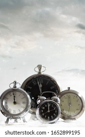 Group of clocks against a snowy cloud background