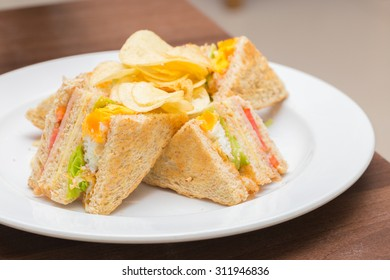Group of club sandwiches with fried egg ,ham and cheese butter on white bread.