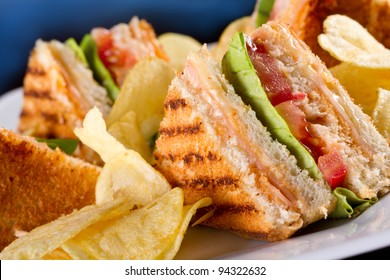 Group of club sandwiches with salmon and cucumbers on white bread