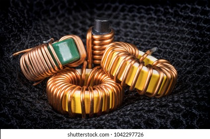 Group of coils with magnetic core and copper winding. Beautiful close-up of three toroidal inductors and one solenoid on background from black hexagonal mesh.
