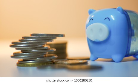 Group of coin with blue pig on blurred background in saving money concept.