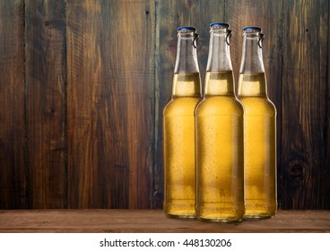Group of cold wet beer bottles on the grunge background